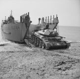 A Crusader I tank emerges from a tank landing craft (TLC 124).