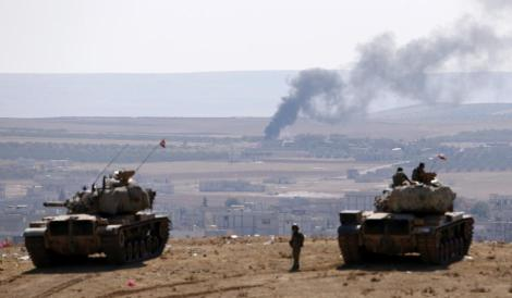 A Turkish Armored Column overlooks Kobani, a Syrian town besieged by ISIS forces. (Reuters)